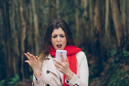 Upset woman looking worried about losing mobile or gps signal coverage on smartphone. Angry brunette girl in trouble or receiving bad news during autumn trip.