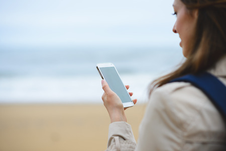 view woman: Woman messaging or video calling on smartphone towards the sea during autumn trip to the beach.