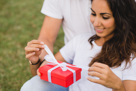 unwrapping: Loving couple celebrating birthday or anniversary with a present. Happy woman unwrapping gift red box. Stock Photo