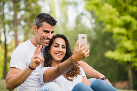 couple dating: Young couple taking a selfie photo with smartphone camera at the park. Man and woman dating on summer or spring.