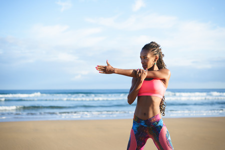 Fitness woman stretching arm and shoulder at the beach. Black female athlete working out outdoor against the sea. Stock Photo