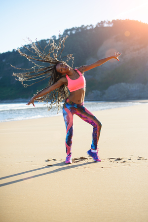 outdoor training: Sporty woman with long hair braids dancing and having fun at the beach on summer sunset. Black happy dancer training outdoor. Stock Photo