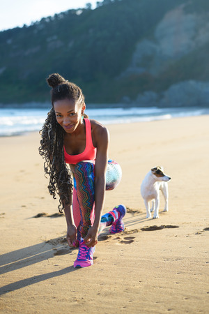 Sporty woman lacing sport footwear before running and exercising at the beach with her dog. Black beautiful runner training outdoor. Stock Photo