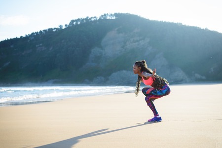 equilibrium: Black fitness woman practicing balance yoga exercise towards the sea during outdoor workout at the beach. Dancing equilibrium training.