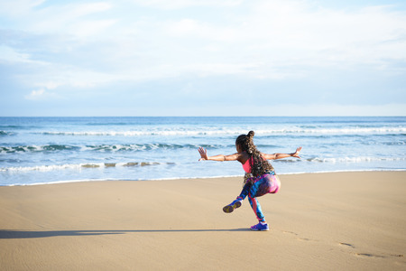 Rückansicht des am Strand Balance Yoga-Übung auf das Meer während des Fitness-Training im Freien Frau praktizieren. Tanzen Gleichgewicht Ausbildung. Standard-Bild - 63818843