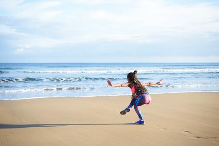 Terug oog van de vrouw het beoefenen van yoga oefening balans in de richting van de zee tijdens fitness outdoor training op het strand. Dancing evenwicht training.