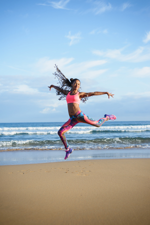 donna che balla: Sporty brazilian woman dancing and jumping at the beach. Black happy dancer practicing dance jumps and having fun outdoor.