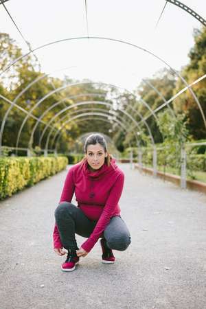 Pregnant sporty woman ready for fitness workout outdoor. Female gravid athlete lacing footwear and getting ready for exercising at the park on early autumn.