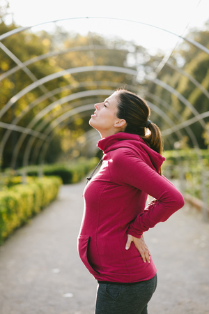 lower back pain: Pregnant fitness woman suffering from lower back pain after training outdoor on early autumn park. Pregnancy lumbago or sciatica. Stock Photo