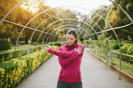 outdoor outside: Fitness pregnant woman doing stretching exercise for arms and shoulder outdoor at urban park on early autumn. Gravid female athlete training outside. Stock Photo