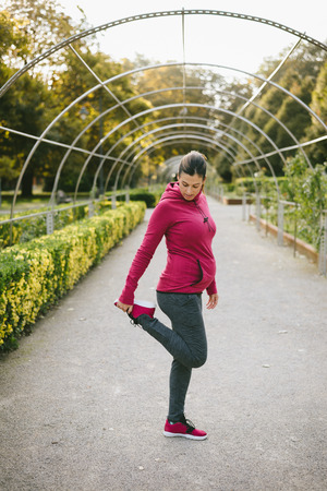 outdoor outside: Fitness pregnant woman stretching legs and exercising outdoor at urban park on early autumn. Gravid female athlete training outside.