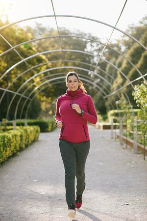 mujer deportista: Mujer embarazada deportivo a correr por el parque en otoño temprano. atleta hembra grávida haciendo ejercicio saludable durante el embarazo para mantenerse en forma.