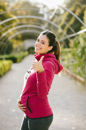 early pregnancy: Sporty pregnant woman doing thumbs up success gesture after urban workout at the park on early autumn. Brunette athlete recommending healthy exercise during pregnancy.