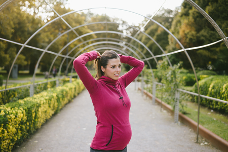 Pregnant sporty woman getting ready for fitness workout outdoor. Female motivated gravid athlete lacing ponytail before training. Stock Photo
