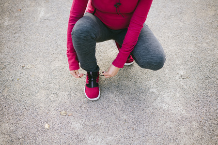 lacing sneakers: Detail of pregnant sporty woman lacing sneakers before jogging or training outdoor. Sport and healthy lifestyle during pregnancy concept