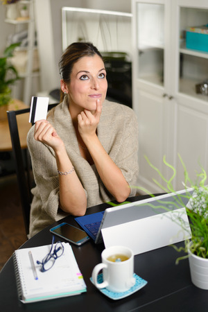 Woman holding credit card and thinking before online shopping on her laptop at home.