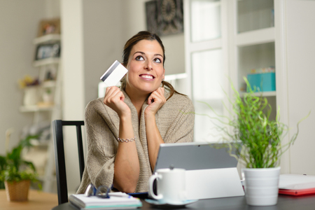 Woman holding credit card and day dreaming before online shopping on her laptop at home.