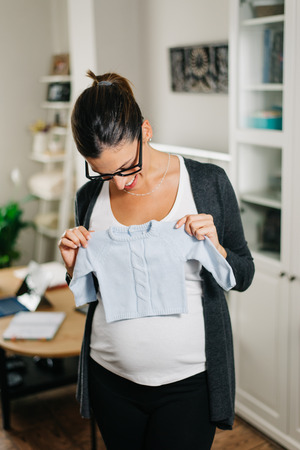boy lady: Happy pregnant woman holding blue baby boy clothes at home. Proud future mother. Stock Photo