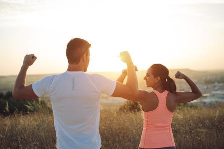 Paare der Sportler Bizeps in den Sonnenuntergang biegt. Ein paar Athleten laufen im Freien Training Erfolg feiern.