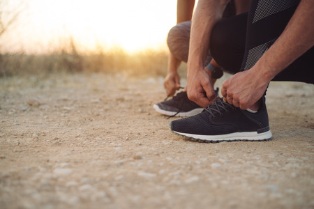 lacing sneakers: Outdoor running concept. Couple lacing sport shoes for preparing for training at sunset. Stock Photo