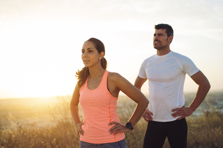 Couple of motivated athletes during outdoor workout. Runners taking a training rest. Stock Photo