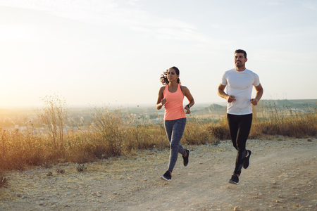 Two athletes running at sunset. Man and woman training together. Stock Photo