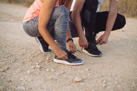 Outdoor running concept. Couple lacing sport shoes before training.