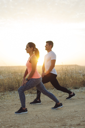 Young couple of athletes stretching legs or doing lunges exercises  for warming up before outdoor running workout at sunset.