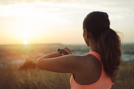 Sportswoman checking running and workout goals on smart watch towards beautiful sunset.