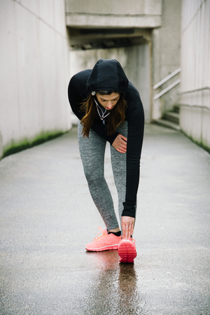 woman stretching: Sporty woman stretching and warming up legs before running urban fitness winter workout. Sport and healthy lifestyle concept. Female athlete exercising outside.