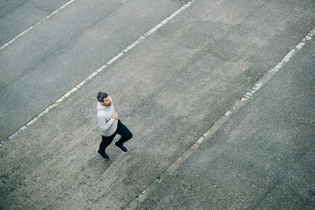 sportsmen: Top view of sporty man running in winter on urban asphalt. Male runner training outside.