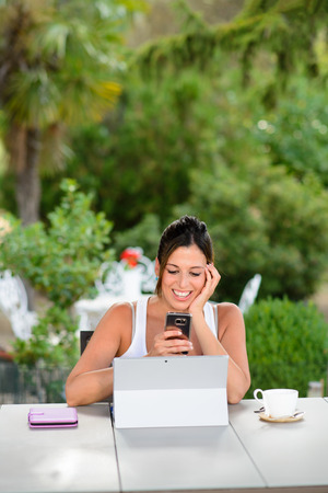 Professional woman using laptop and smartphone outside at garden during summer vacation or leisure time. Female worker using internet technology and modern communications for doing her job online.