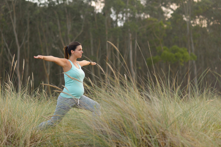 pregnant woman yoga: Pregnant woman on fitness outdoor workout. Pregnancy healthy lifestyle and relaxing yoga exersice.
