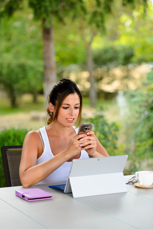 Professional woman using laptop and texting on smartphone outside at garden during summer vacation or leisure time. Female worker using internet technology for doing her job online.