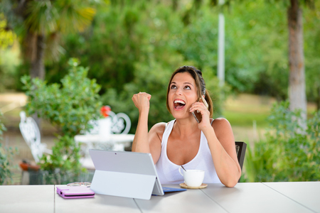 Successful professional woman on cellphone call and using laptop outside at garden during summer vacation or leisure time. Female worker using internet technology for doing her job online.
