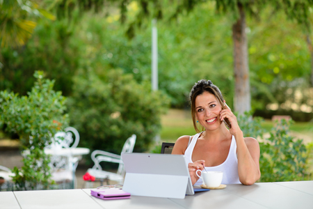 Relaxed woman using laptop outside at garden during summer vacation or leisure time. Female casual worker using internet technology and modern communications for doing her job online.