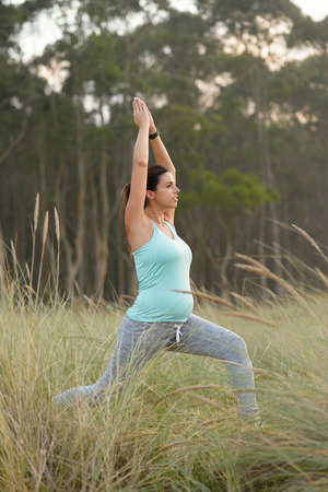 breathing exercise: Pregnant woman on fitness outdoor workout. Pregnancy healthy lifestyle and relaxing yoga breathing exercise. Stock Photo