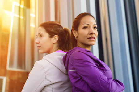 crossing arms: Sport and fitness workout motivation. Two successful motivated urban sporty women crossing arms.