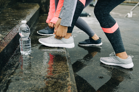 Urban athletes lacing sport footwear for running in the city under the rain. Two women getting ready for outdoor training and fitness exercising on cold winter weather. Stock Photo