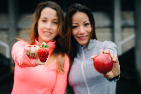 nutritive: Two sporty women showing strawberry and red apple. Healthy fitness diet concept. Nutritive fruit for eating during workout break. Stock Photo