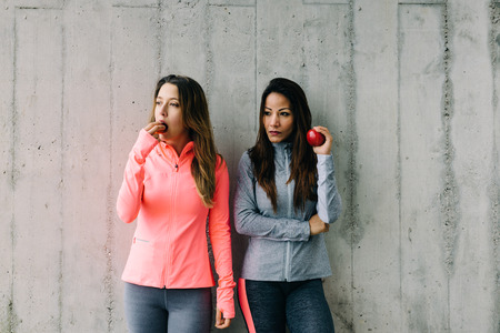 multiracial: Two women taking a workout rest for eating healthy fruits. Fitness diet and lifestyle concept.