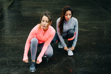 rain weather: Urban athletes lacing sport footwear for running over asphalt under the rain. Two women getting ready for outdoor training and fitness exercising on cold winter weather. Stock Photo