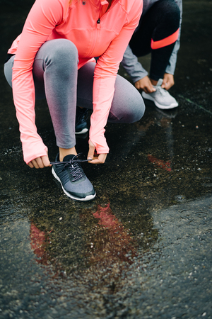 lacing sneakers: Detail of urban athletes lacing sport footwear for running over asphalt under the rain. Two women getting ready for outdoor training and fitness exercising on cold winter weather.