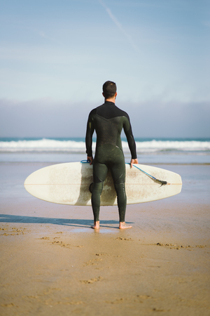 male surfer: Back view of male surfer looking for waves before surfing. Outdoor beach water sport and surf lifestyle.