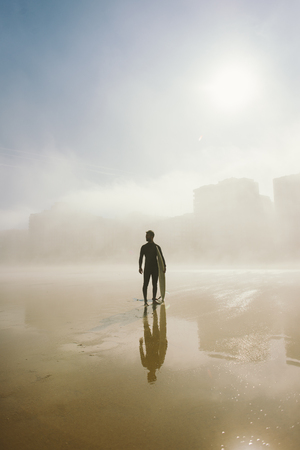 outdoor sport: Surfer holding his surfboard and looking for waves on a misty urban beach. Outdoor beach water sport and surf lifestyle.