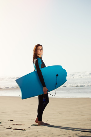 Female surfer beach lifestyle portrait. Woman in wetsuit with bodyboard surfing equipment.