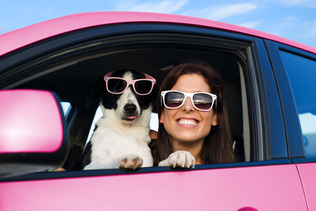 Woman and dog in pink car on summer road trip vacation. Funny dog with sunglasses traveling. Travel with pet concept. Standard-Bild