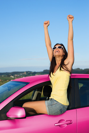 driving a car: Joyful woman having fun with her new pink car raising arms up to the sky on summer road trip vacation. Freedom and driving license success concept.