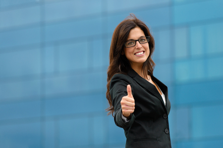 Professional businesswoman doing thumbs up gesture against corporate building outside. Female business success and job goals.