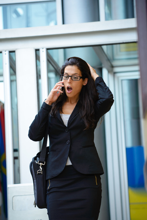 business problems: Worried business woman on the phone. Job problems and stressful modern professional lifestyle.